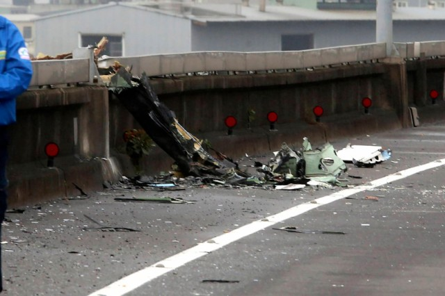 A man walks past next to the wreckage of a TransAsia Airways plane which hit a motorway before crash landing in a river, in New Taipei City
